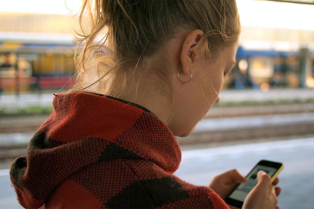 Una joven mira el móvil.